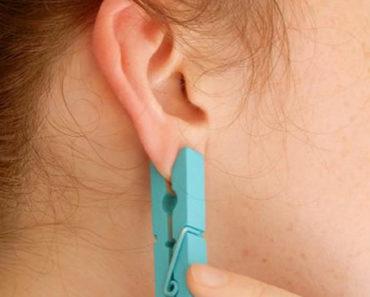 colocar um prendedor de roupas na orelha